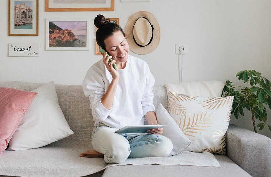 a-young-woman-wearing-white-sweatshirt-and-blue-jeans-is-working-from-home-using-a-mobile-phone-and-a_t20_VW1RG6
