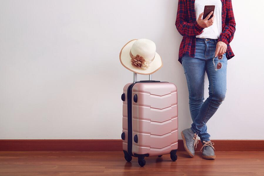 asian-woman-traveler-looking-at-smart-phone-carry-pink-luggage-with-hat_t20_W7odEL